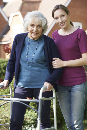two people: Daughter Helping Senior Mother To Use Walking Frame