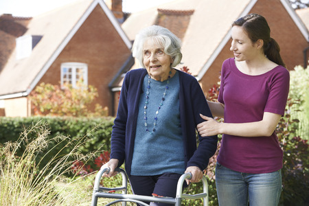 dementia: Daughter Helping Senior Mother To Use Walking Frame