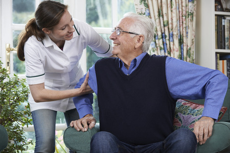 an elderly person: Cuidado trabajador ayuda al hombre mayor que levantarse de la silla Foto de archivo