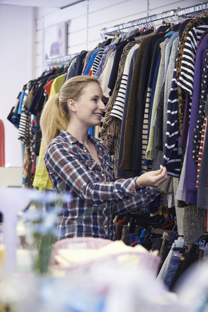 thrift: Female Shopper In Thrift Store Looking At Clothes