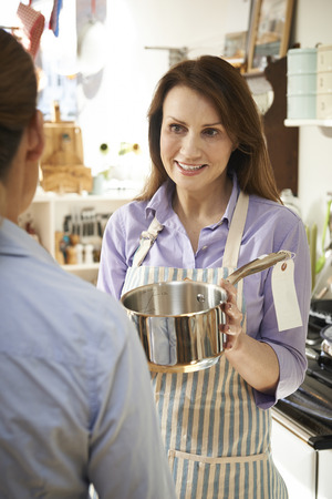 sales assistant: Sales Assistant In Homeware Shop Showing Customer Pan