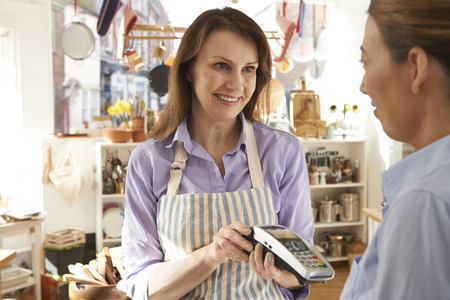 homeware: Customer Paying In Kitchen Shop Using Credit Card Terminal