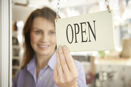female business: Store Owner Turning Open Sign In Shop Doorway