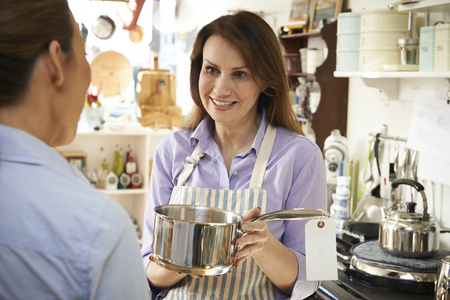 Sales Assistant In Homeware Shop Showing Customer Pan photo