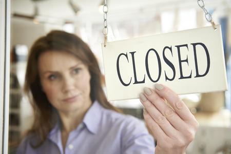 Store Owner Turning Closed Sign In Shop Doorway Standard-Bild