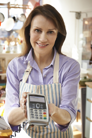 sales assistant: Sales Assistant In Homeware Store With Credit Card Machine Stock Photo