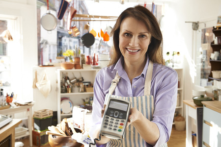 small business owner: Sales Assistant In Homeware Store With Credit Card Machine Stock Photo