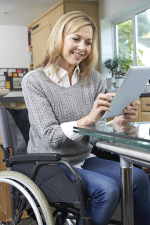 fila de personas: Disabled Woman In Wheelchair Using Digital Tablet At Home