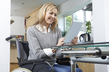 e work: Disabled Woman In Wheelchair Using Digital Tablet At Home