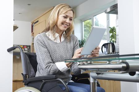 persona en silla de ruedas: La mujer con discapacidad en silla de ruedas con la tableta digital en el hogar