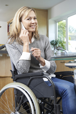 trabajando en casa: Disabled Woman In Wheelchair Making Call On Mobile Phone At Home