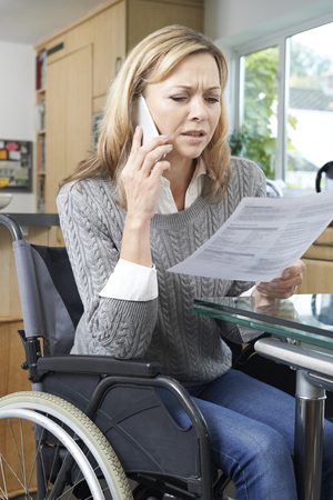 phone call: Frustrated Woman In Wheelchair Making Phone Call Whilst Reading Letter