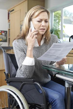 persona triste: Mujer frustrada en la fabricación de sillas de ruedas llamada de teléfono Mientras Carta de la lectura
