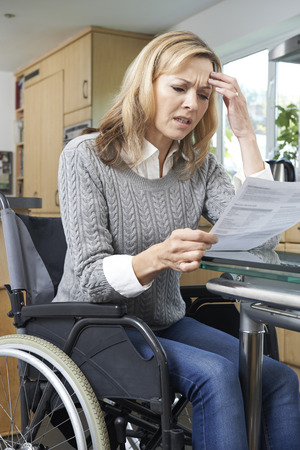 discapacidad: Mujer frustrada en la silla de ruedas de leer la carta