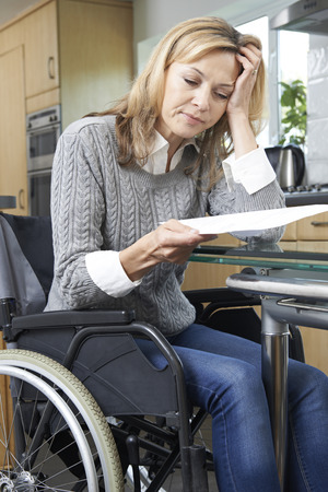 disability insurance: Frustrated Woman In Wheelchair Reading Letter
