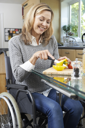 disabled person: Disabled Woman In Wheelchair Prepapring Meal In Kitchen