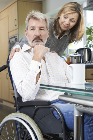 comforting: Woman Comforting Depressed Man In Wheelchair At Home Stock Photo