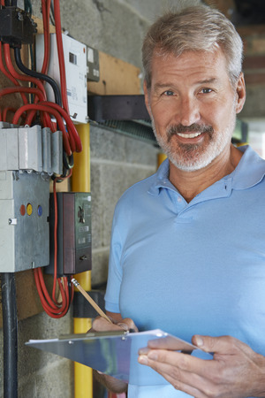 mature man: Portrait Of Electrician Standing Next To Fuseboard Stock Photo