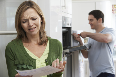 dissatisfaction: Unhappy Female Customer With Oven Repair Bill Stock Photo
