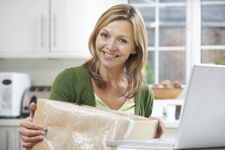 online purchase: Happy Woman Unpacking Online Purchase At Home