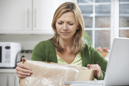 purchase: Disappointed Woman Unpacking Online Purchase At Home