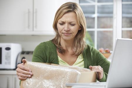 Enttäuschte Frau Auspacken Online-Kauf zu Hause