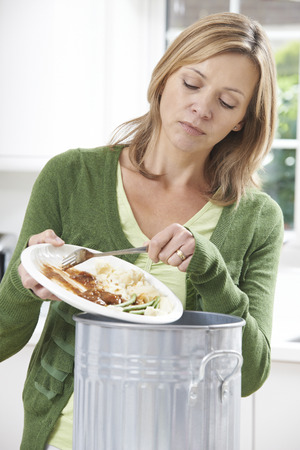 comida: Raspa de la mujer de comida sobras en Tacho de la basura