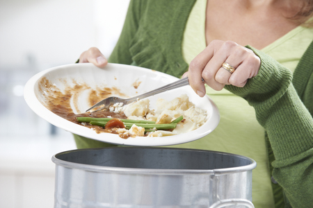 garbage: Woman Scraping Food Leftovers Into Garbage Bin Stock Photo