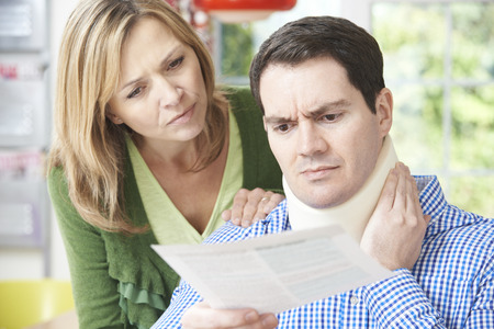Couple Reading Letter In Respect Of Husband's Neck Injury Stockfoto