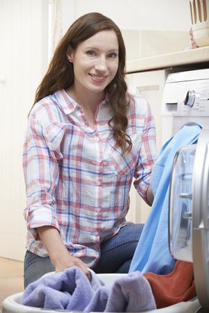 doing laundry: Portrait Of Woman Doing Laundry At Home