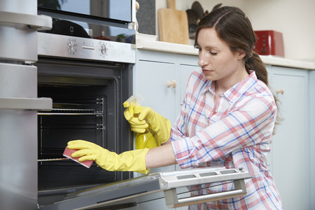 cleaning kitchen: Fed Up Woman Cleaning Oven At Home Stock Photo
