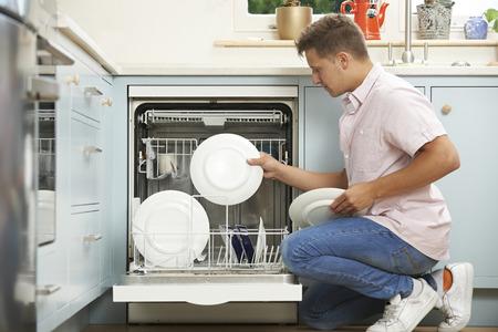 trabajando en casa: Hombre Cargando lavavajillas en cocina