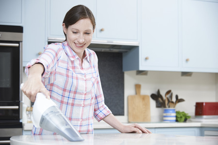 hand held: Woman Cleaning Kitchen Using Hand Held Vacuum Cleaner Stock Photo