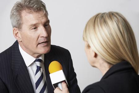 Businessman Being Interviewed By Female Journalist With Microphone Foto de archivo