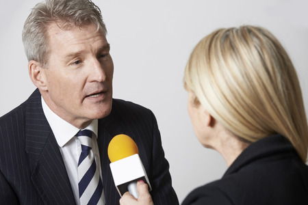 Businessman Being Interviewed By Female Journalist With Microphone Stockfoto