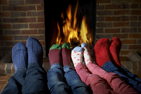 Family Wearing Socks Warming Feet By Fire Archivio Fotografico
