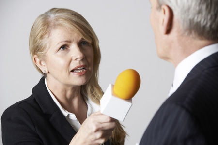 tv reporter: Female Journalist With Microphone Interviewing Businessman Stock Photo