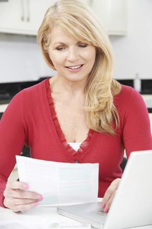 mature women: Smiling Mature Woman Reviewing Domestic Finances