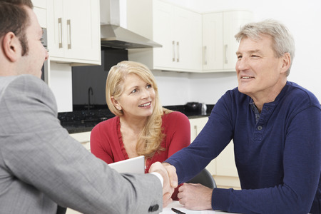 advice: Mature Couple Shaking Hands With Financial Advisor At Home Stock Photo
