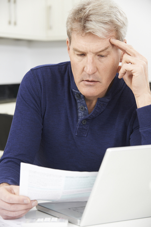 home finances: Worried Mature Man Looking Reviewing Finances At Home Stock Photo