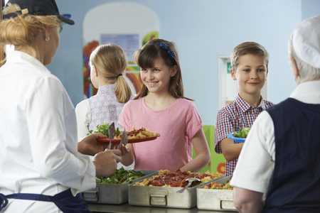school cafeteria: Pupils Being Served With Healthy Lunch In School Canteen Stock Photo