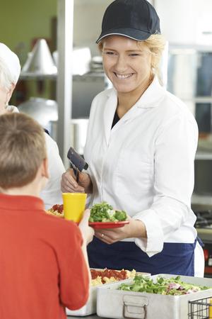 almuerzo: Alumno en cafeter�a de escuela Estar almuerzo servido por Cena Se�ora