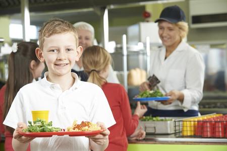 comedor escolar: Alumno de sexo masculino con almuerzo saludable en la cafetería de la escuela