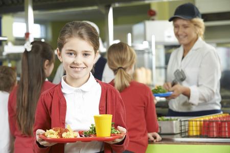 uniformes: Alumno Mujer Con El almuerzo saludable en la cafeter�a de la escuela Foto de archivo