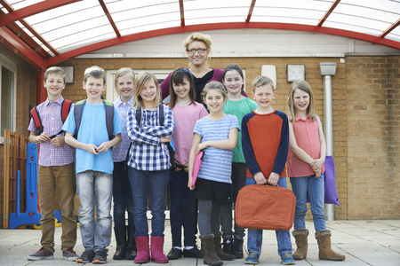 old people group: Portrait Of Teacher With Pupils In Playground Stock Photo