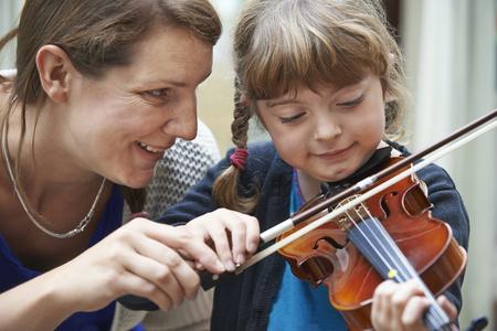 salle de classe: Enseignant Aider les jeunes Femme �l�ves en violon Le�on