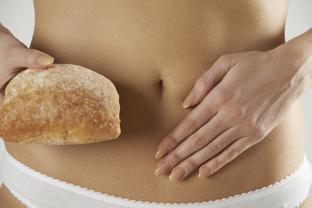 stomach: Close Up Of Wheat Intolerant Woman Holding Bread Stock Photo