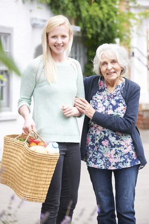assist: Teenage Girl Helping Senior Woman To Carry Shopping Stock Photo