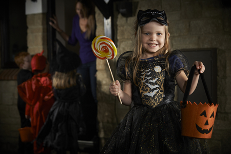 treating: Halloween Party With Children Trick Or Treating In Costume