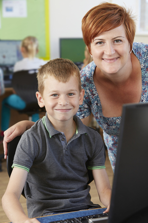 Male Elementary Pupil In Computer Class With Teacher photo